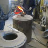Molten bronze being cast into investment mold under vacuum